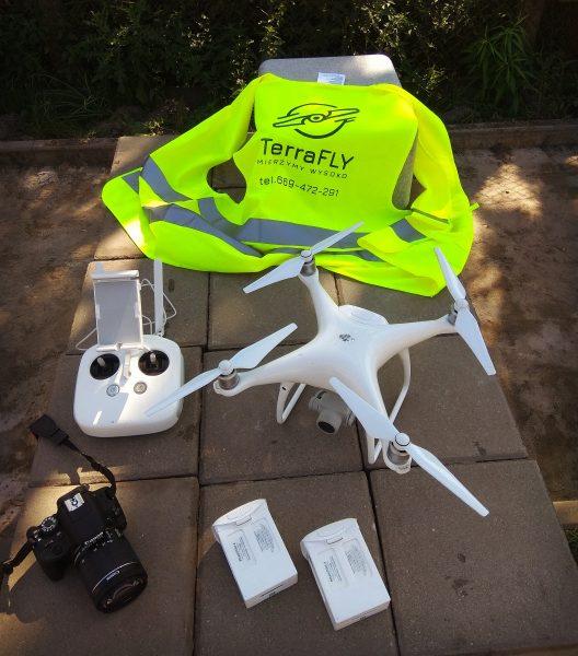 Dron, baterie, aparat fotograficzny i kamizelka ofblaskowa
